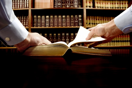 Photo pour Hands holding an old book with library in background - image libre de droit