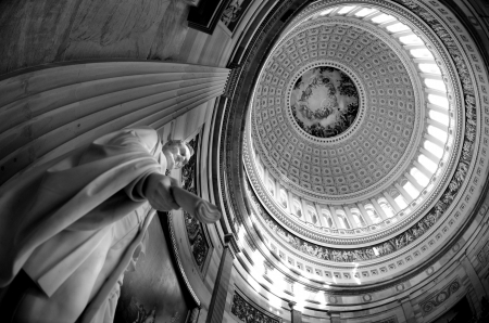 Inside of US Capitol Building with dome and statue of Abraham Lincoln holding document