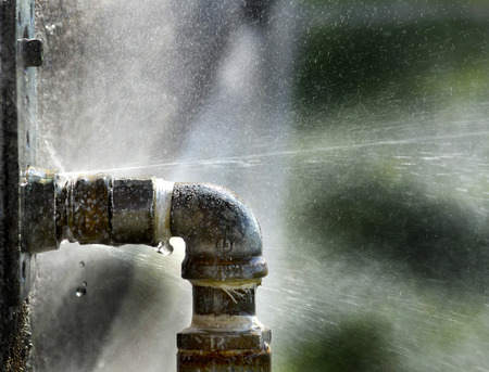 Photo for Old rusty pipe with leak and water spraying out - Royalty Free Image