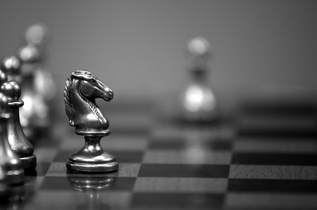 Photo pour Chess board with white knight facing opponent in match - image libre de droit