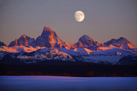 Foto de Sunset light with alpen glow on Tetons Teton mountains rugged with moon rising - Imagen libre de derechos