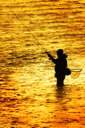 Photo pour Silhouette of Fishing Flyfishing rod reel in river with golden sunlight surrounding him early morning fisherman - image libre de droit