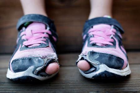 Photo for Homeless child wearing old worn out shoes on feet with holes in them toes sticking out - Royalty Free Image