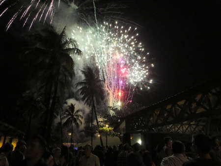 Honolulu - December 31, 2013: New Years Fireworks burst in the air as people watch display at Outdoor New Years Party December 31, 2013 in Honolulu, Hawaii.