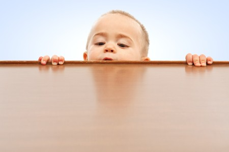 Curious little boy climbing up and looking onto table surface