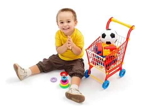 Foto de Happy little boy sitting on ground, and playing. New toys in small shopping cart - Imagen libre de derechos