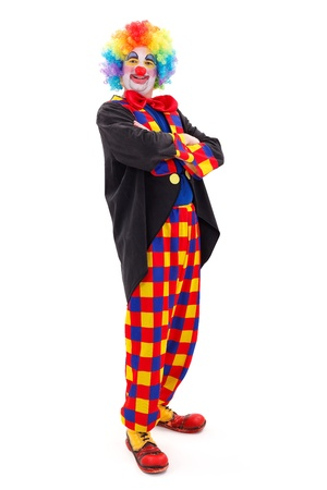Proud clown in colorful wearing, standing with folded arms on white background