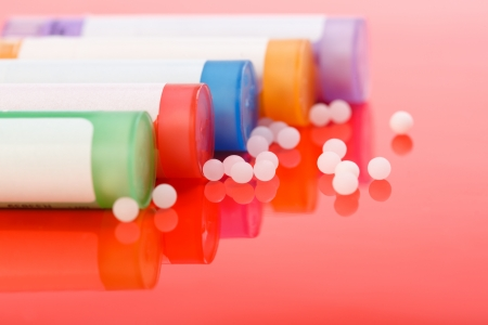 Colorful homeopathic pills and containers on reflective red background