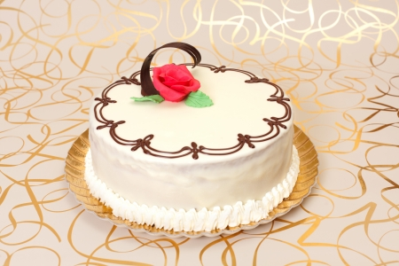 White cake with chocolate ornaments and red marzipan rose