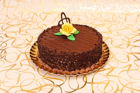 Chocolate cake on golden plate with orange marzipan rose