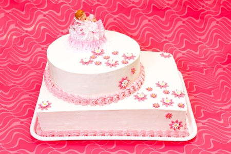 White christening cake for girl with pink decoration