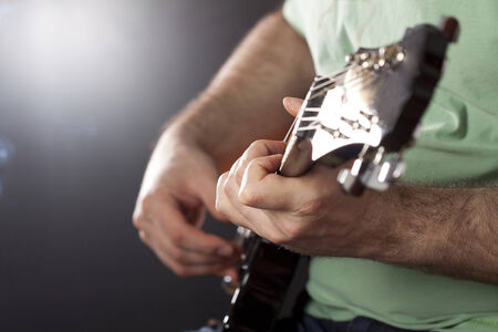 Man playing les paul electric guitar is studio