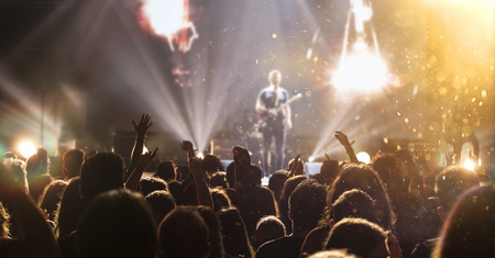 Photo pour Crowd at concert - Cheering crowd in bright colorful stage lights - image libre de droit