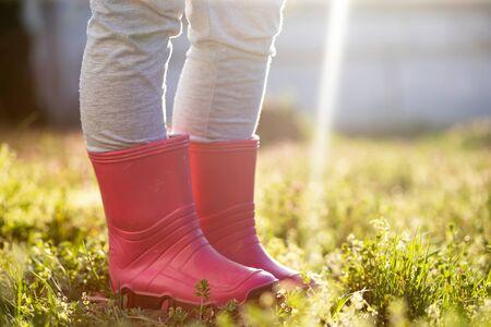 Photo pour Child leg in pink wellington boots standing in magic spring garden. - image libre de droit