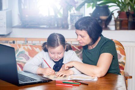 Foto de Distance learning-online education. School girl with her mother doing school homework. COVID-19 pandemic forces children online learning. - Imagen libre de derechos