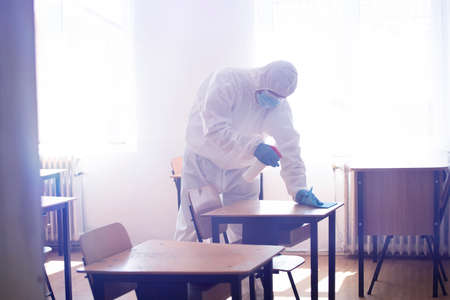 Foto de Worker sprays disinfectant as part of preventive measures against the spread of the COVID-19, the novel coronavirus in schools. Preparing for the new school season. - Imagen libre de derechos