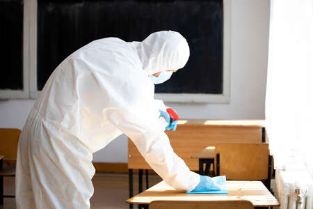 Photo for Worker sprays disinfectant as part of preventive measures against the spread of the COVID-19, the novel coronavirus in schools. Preparing for the new school season. - Royalty Free Image
