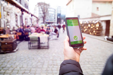 Photo pour Vaccinated person using immunization certificate on smartphone at the restaurant or terrace. - image libre de droit