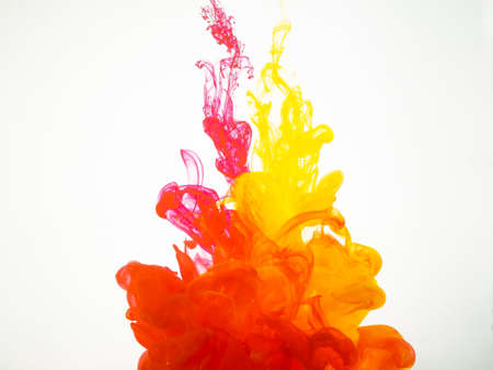 Foto de Movement of acrylic colours in water photographed while in motion. Abstract swirling of ink in water. Splash of ink isolated on white background. Yellow-red acrylic colour dissipation - Imagen libre de derechos