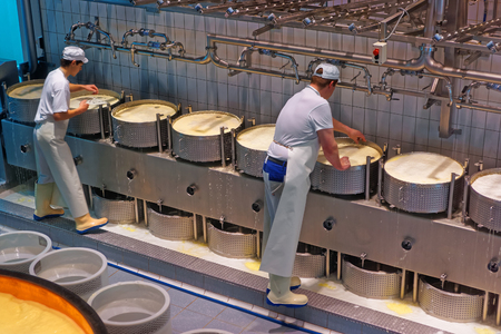 GRUYERE, SWITZERLAND - DECEMBER 31, 2014: Workers during the process of production of Gruyere cheese at the Maison du Gruyere, a famous cheese-making factory in Switzerland