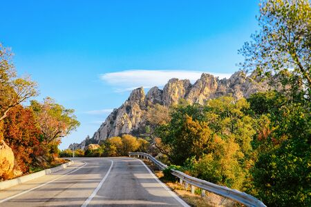Photo pour Empty road without cars, in Sardinia Island in Italy in summer. Panorama with highway and green nature and blue sky. Mountains on the background. - image libre de droit