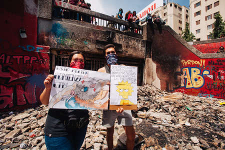 SANTIAGO, CHILE-OCTOBER 29, 2019 - A couple of students show their proclamations in the ruins of the Baquedano Metro Station, vandalized during several days of protests in Chile