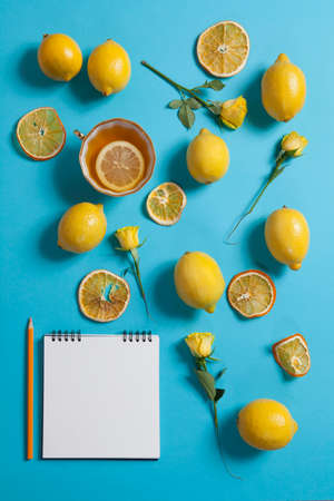Tropical pattern from cup of tea, roses and lemons different sizes scattered on a blue background. Fresh design for printing The summer theme. Copyspace