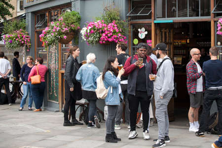 LONDON, ENGLAND - August 11 2017 A motley crowd sits outside the pub, drinks beer, talks with friends. Borough market
