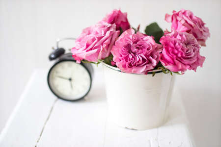 Photo for A bouquet of pink roses in a tin white bucket on an old stool with an alarm clock and a napkin with embroidery near the bed on a beige background - Royalty Free Image