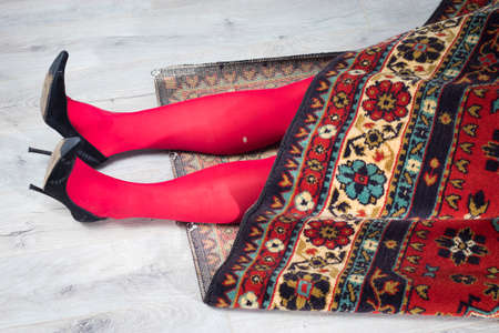 Photo for Legs in red tights with a hole wrapped in a traditional rug. crime scene - Royalty Free Image