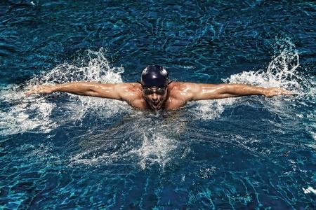 Photo pour portrait of young man swimming in pool - image libre de droit