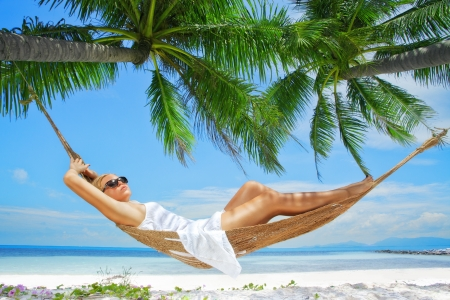 Photo pour view of nice young lady swinging  in hummock on tropical beach - image libre de droit