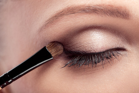 makeup artist deals makeup brush for eyes. makeup for a young beautiful girl. brown eye shadow. close up