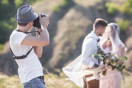 Foto de a wedding photographer takes pictures of the bride and groom in nature, the photographer in action - Imagen libre de derechos