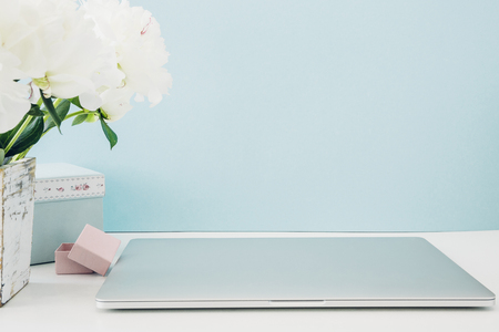 Laptop with white blank screen and flowers in vase on table on blue background. mock up
