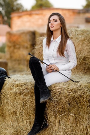 rider woman with whip is sitting on hay