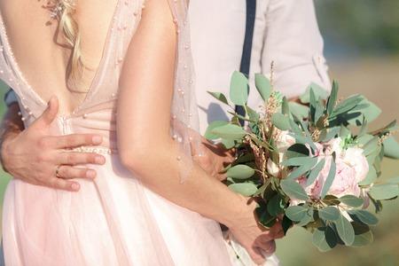 Foto de Hands of the bride and groom with wedding bouquet - Imagen libre de derechos