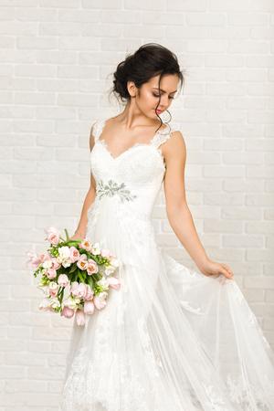 Foto de Portrait of beautiful bride with wedding bouquet of pink tulips - Imagen libre de derechos