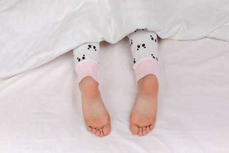 Photo pour Pair of kid bare feet in bed on white sheets - image libre de droit
