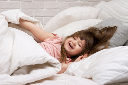 Photo pour cute little child girl wakes up from sleep in bed in the morning - image libre de droit