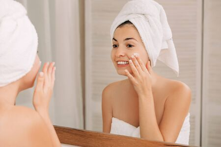 Photo pour Portrait of beautiful woman caring of her skin. girl looking at mirror and applying cream on her face in front of the mirror in bathroom - image libre de droit