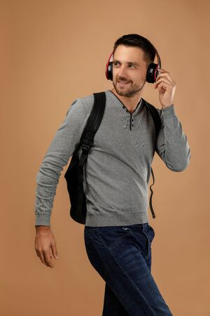 Photo pour handsome young man in headphones with backpack listens to music isolated on beige background. - image libre de droit