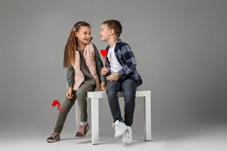 Photo pour happy smiling stylish little couple child girl and boy with red hearts on stick in fashionable clothes sittting together at studio. St. Valentines Day. - image libre de droit