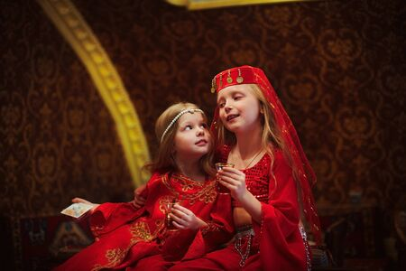 Photo pour Two girls in folk Arabic costumes drinking Turkish tea together - image libre de droit