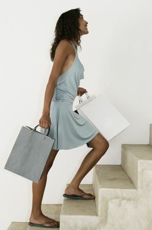 Female walking up stairs with shopping bags