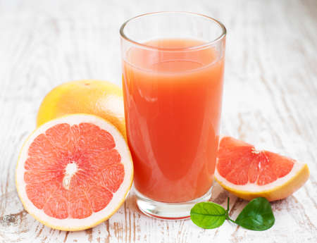 Grapefruit juice and ripe grapefruits on a wooden