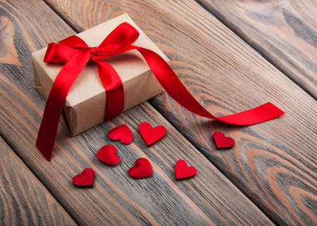 Photo pour Gift box and hearts on a old wooden background - image libre de droit