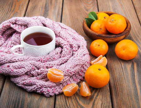 Cup of tea with scarf and tangerines on a old wooden table