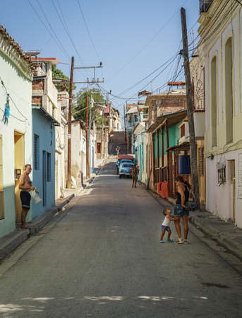 Santiago de Cuba, Cuba - January 10, 2016: Typical scene of one of streets in the center of Santiago de cuba - Colorful architecture, people walking around. Santiago is the 2nd largest city in Cuba