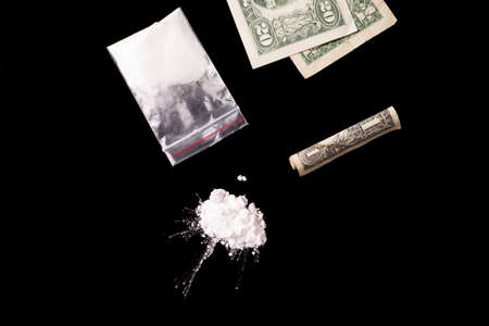 cocaine, Herion or other illegal drugs that are sniffed by means of a tube or injected with a syringe and money, isolated on black glossy background